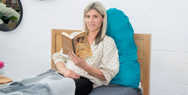 Pyramid Pillow Slip womenb sitting on the bed reading a book