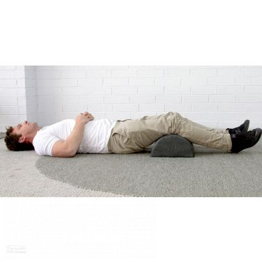 Theramed Lumbar Bolster large D Shape man lying on the ground with bolster under his knees