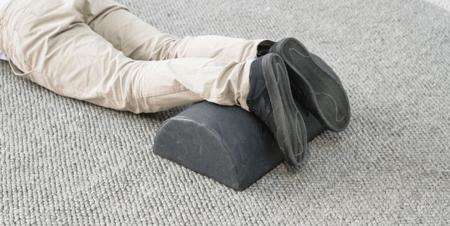 Theramed Lumbar Bolster large D Shape man lying on the groun face down with feet up