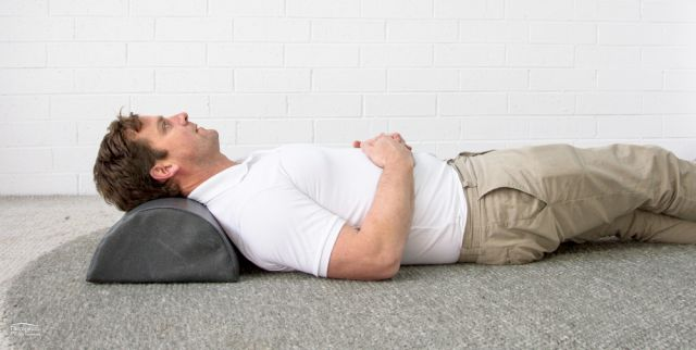 Theramed Lumbar Bolster large D Shape man lying on his back on the ground with bolster under his neck